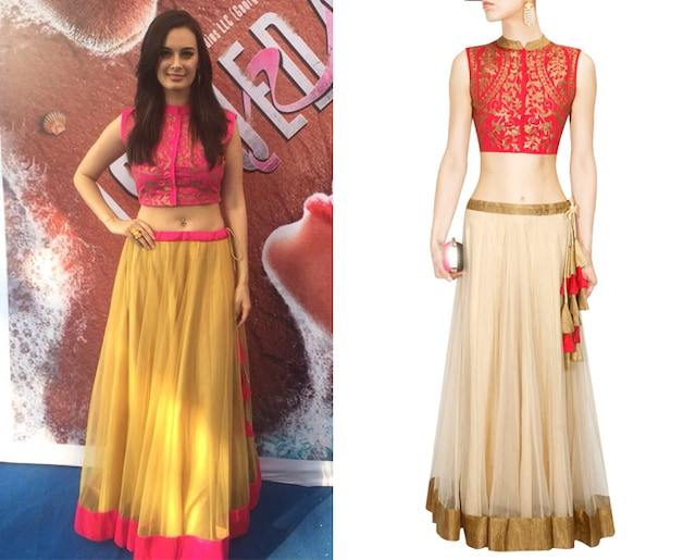 Orange sequins embellished crop top with off white lehenga by Vasavi Shah