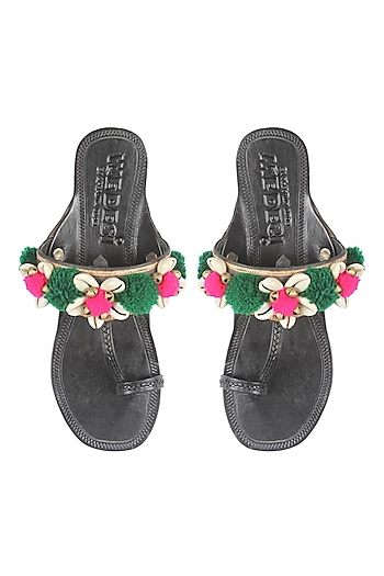 Black kolhapuri flats with green and pink pompoms by Aprajita Toor