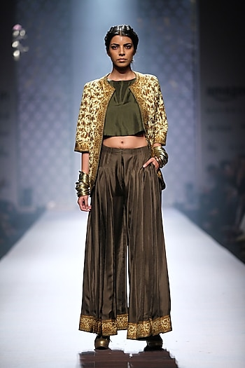 Pale green printed quilt jacket with lose crop top and olive green flared pants by Ashima Leena