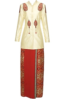 Ivory paisley printed mandarin collared jacket and red wrap around skirt set by Ashima Leena