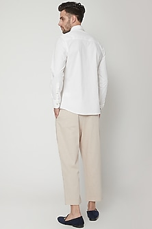 Natural Beige Pleated Trousers by Genes Lecoanet Hemant Men