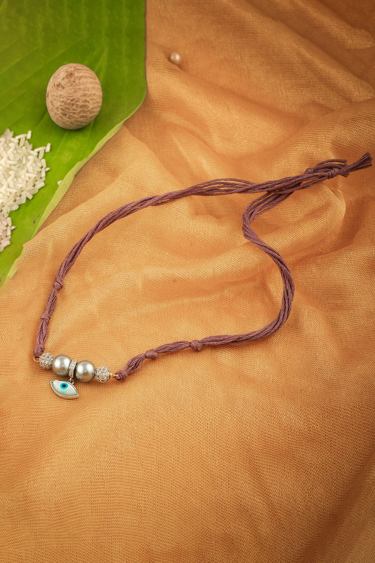 Rose Gold Finish Evil Eye Rakhi With Shell Pearl by Joules By Radhika