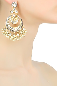 Gold plated kundan and pearl coupled crescent earrings by Nepra By Neha Goel