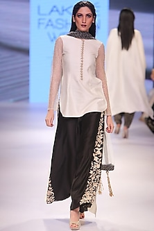 Cream embroidered short kurta with black embellished palazzos and cream dupatta. by Payal Singhal