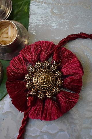 Gold Finish Rakhi With Red Threadwork by Sonnet